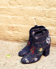 Pair of blue floral booties on the street up against a brick wall.
