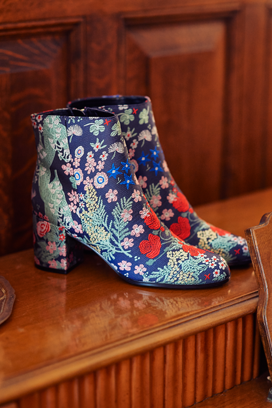 Pair of floral pattern booties on a tabletop.