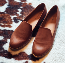 Pair of brown loafers on carpet.