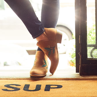 "Woman's feet wearing booties standing on welcome mat with saying ""sup"" on it."