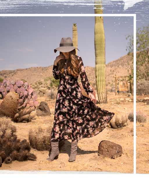 A girl in a long dress wearing brown boots in a desert scene.