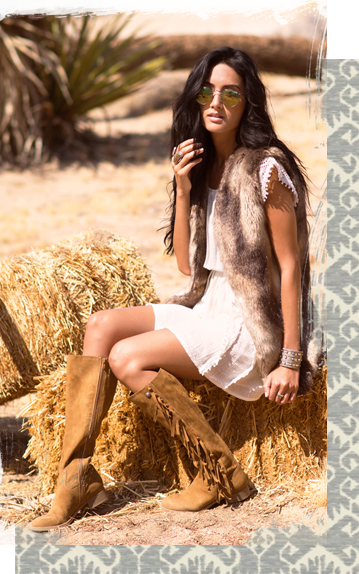 A girl sitting on a bail of hay, wearing brown tassel boots.