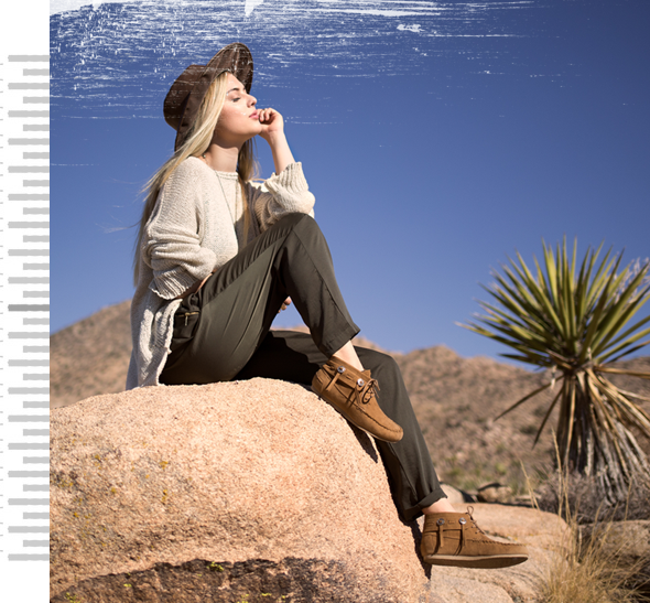A girl sitting on the top of a large rock wearing brown moccasins in the desert.