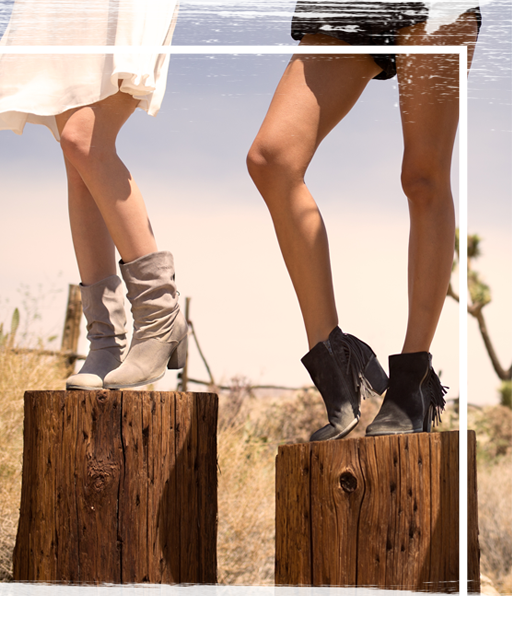 Two sets of legs standing on trunks of trees wearing boots in the desert.