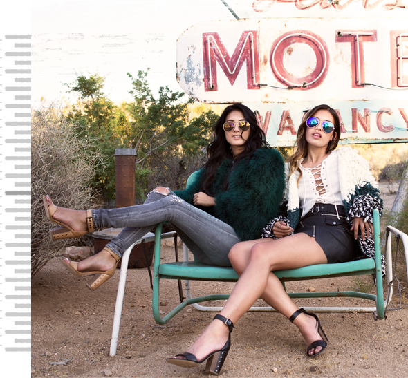 Two cool girls sitting on a bench in front of hotel sign wearing sandals.