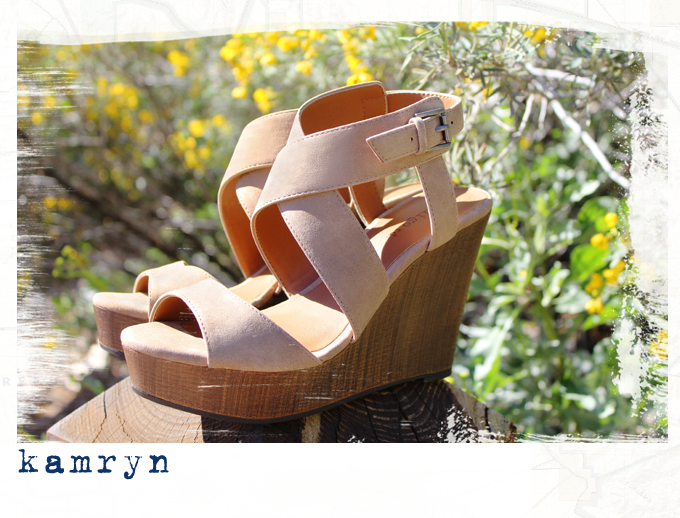 Pair of Kamryn sandals sitting on wood with a floral background.