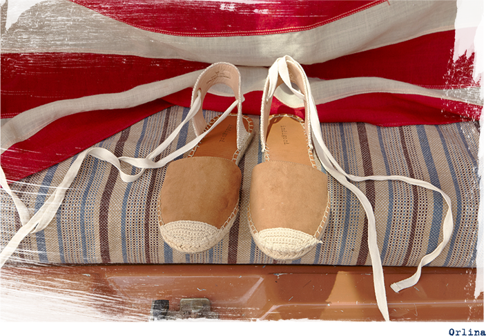 Pair of untied Orlina sitting on fabric with flag background.