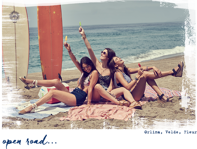 Girls on beach with surfboards and ice pops wearing sandals.