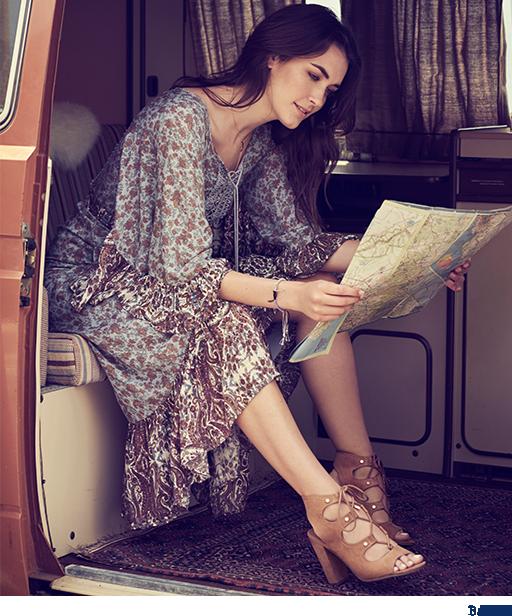 Girl inside van reading a map.