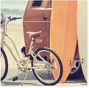 Bike, surfboard and back of van with beach background.