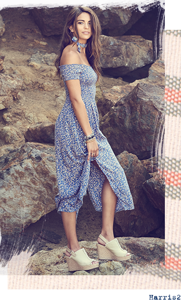 Girl in blue dress wearing white sandals with rocks in the background.