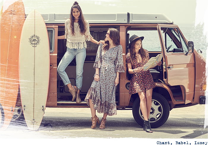 Girls standing outside of their van with surfboards and a map.